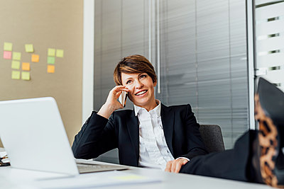 Happy businesswoman looking away while talking on smart phone at desk - p300m2275763 by Eugenio Marongiu