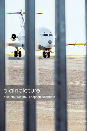 An old jet aircraft standing on the outskirts of an airfield behind a large metal security fence. - p1057m2141784 by Stephen Shepherd