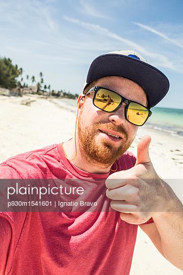 Urlauber mit Sonnenbrille hebt den Daumen - p930m1541601 von Ignatio Bravo