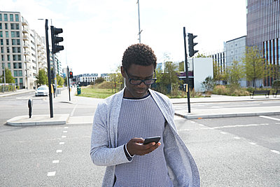 Male professional using mobile phone on street in city - p300m2241576 von Pete Muller
