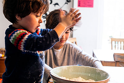 Boys playing with flour in mixing bowl - p429m2078699 by Bonfanti Diego