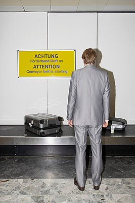 Man waiting for his suitcase - p4641059 by Elektrons 08
