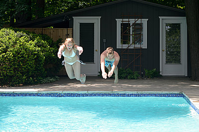 Couple diving into swimming pool in backyard - p555m1409777 by Shestock