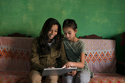 Aunt and niece using digital tablet on sofa - p555m1413074 by Donald Iain Smith