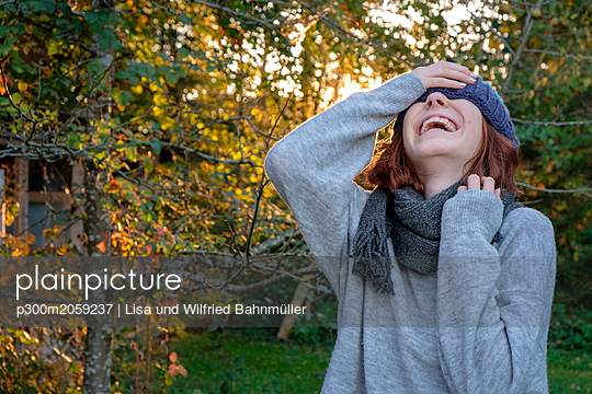 Laughing teenage girl wearing wooly hat and scarf in autumn - p300m2059237 by Lisa und Wilfried Bahnmüller