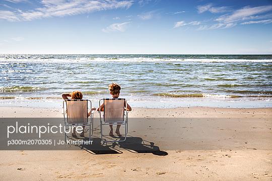 Netherlands, Zandvoort, boy and girl sitting on chairs on the beach - p300m2070305 by Jo Kirchherr