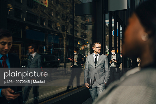Businessman with hand in pocket on sunny day during pandemic - p426m2270345 by Maskot