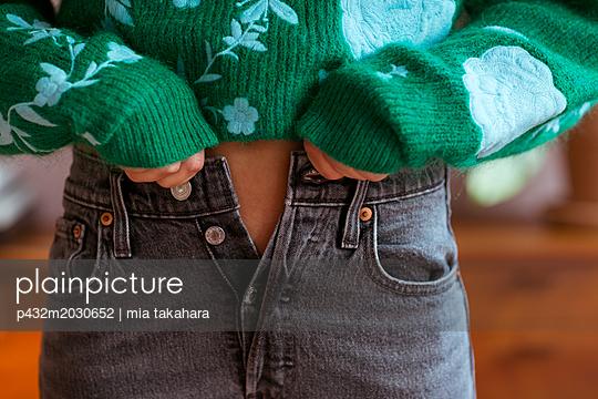 Junge Frau mit offener Jeanshose - p432m2030652 von mia takahara