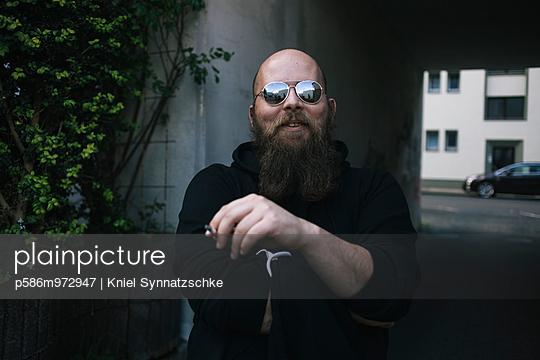 Mann mit Bart und Sonnenbrille raucht eine Zigarette - p586m972947 von Kniel Synnatzschke
