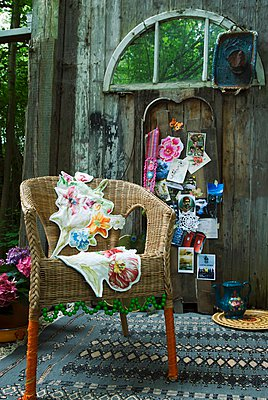"""""""Wicker chair decorated with green beads and floral cushions on patterned rug; colourful postcards and memorabilia on old barn wall"""" - p1183m996837 by Manduzio, Matteo"""
