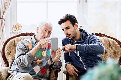 Caretaker assisting elderly man in using mobile phone at nursing home - p426m1131137f by Maskot