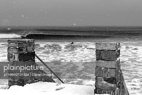 A surfer paddles out alone during snowstorm - p1166m2131334 by Cavan Images