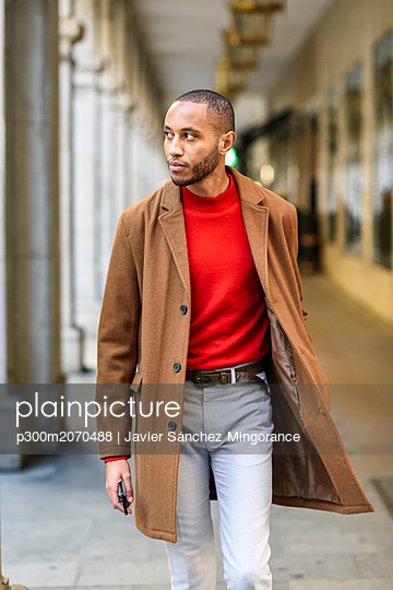 Fashionable young man wearing red pullover and brown coat walking along arcade - p300m2070488 by Javier Sánchez Mingorance