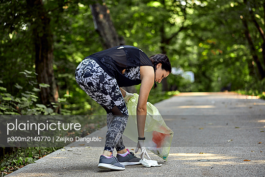 Young woman plogging on forest path - p300m2140770 by Zeljko Dangubic