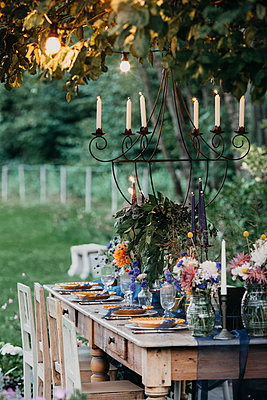 Festive laid table with candles under a tree - p300m2059831 by Alberto Bogo