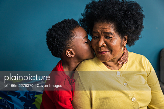 Grandson lovingly kissing his grandmother on the cheek - p1166m2279370 by Cavan Images