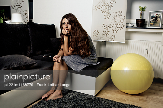 Junge Frau sitzt auf dem Sofa - p1221m1168779 von Frank Lothar Lange