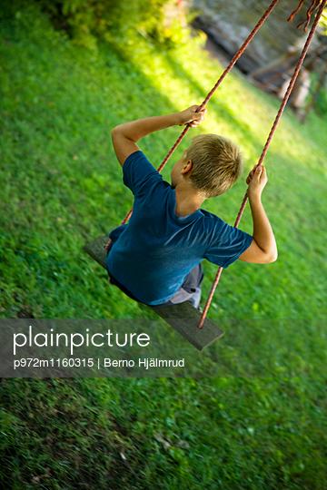 Junge auf einer Schaukel - p972m1160315 von Berno Hjälmrud