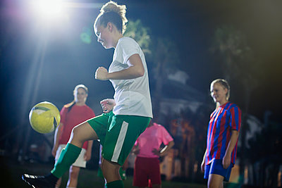 Young female soccer player kicking the ball, practicing on field at night - p1023m1542451 by Sam Edwards