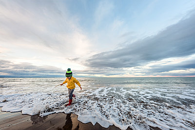 Preschooler running in water with boots and hat in New Zealand - p1166m2165970 by Cavan Images