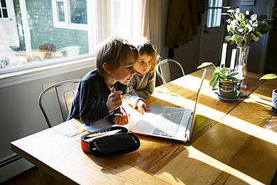 kids in morning light sitting at table doing remote school - p1166m2232749 by Cavan Images