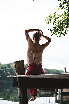 non-binary person ties hair in sunlit jetty over beautiful green lake - p1166m2290072 by Cavan Images