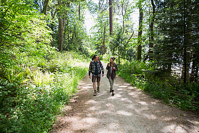 Couple hiking trail in woods - p1192m1149348 by Hero Images