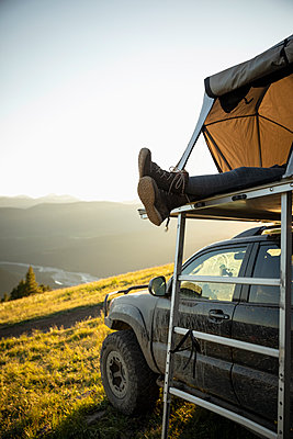 Womans feet dangling from SUV rooftop tent in idyllic mountain field, Alberta, Canada - p1192m2016500 by Hero Images