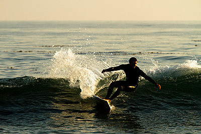 A male surfer rips a turn while surfing in Malibu, California. - p1424m1501547 by Kyle Sparks