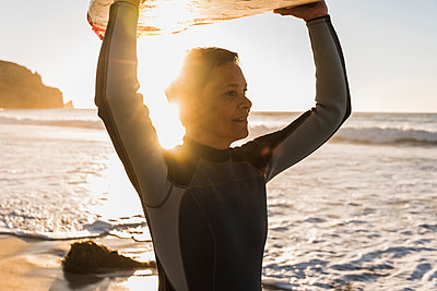 France, Bretagne, Crozon peninsula, woman on beach at sunset carrying surfboard - p300m1189457 by Uwe Umstätter