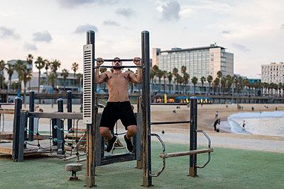 Barechested muscular man doing chin-ups on the beach - p300m2080910 von Mauro Grigollo