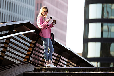Young businesswoman using smartphone and holding coffee to go - p300m2114521 by Josep Suria
