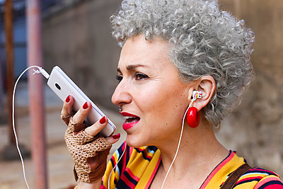 Portrait of pierced mature woman with grey curly hair using earphones and cell phone - p300m2132416 by Retales Botijero