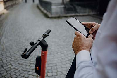 Businessman renting an e-scooter using smartphone - p300m2140059 by Johanna Lohr