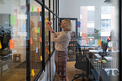 Mature businesswoman writing on adhesive notes on glass pane in office - p300m2156045 by Gustafsson