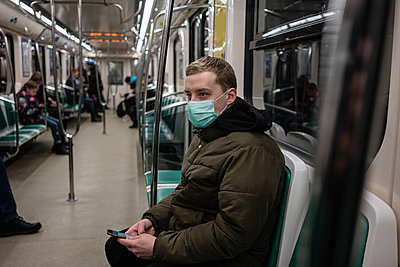 Young man in commuter train, wearing face mask, using smartphone - p300m2170817 by Vasily Pindyurin