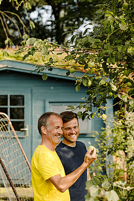 Smiling father and son examining granny smith apple in backyard - p300m2276944 by Gustafsson