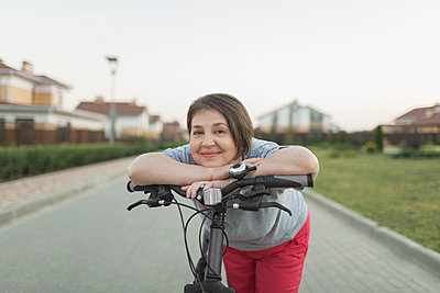 Portrait of senior woman leaning over bicycle handle on street - p301m1498587 by Vladimir Godnik