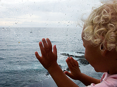 Girl looking through window onto the sea - p972m1160341 by Sesse Lind
