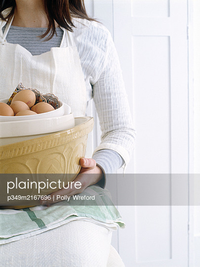 Woman holds mixing bowl and eggs in preparation for baking  - p349m2167696 by Polly Wreford