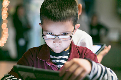 A little boy with glasses draws a digital art on his tablet - p1166m2202290 by Robert benson