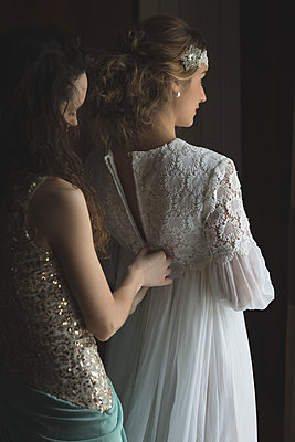 Bridesmaid assisting bride to dress - p1315m1484306 by Wavebreak