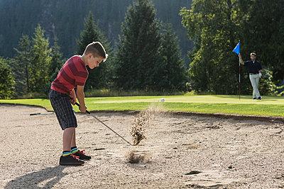 Boy taking a shot in the golf course - p1315m1565183 by Wavebreak