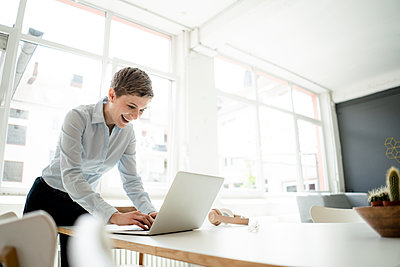 Happy businesswoman using laptop on table in office - p300m2140455 by Kniel Synnatzschke