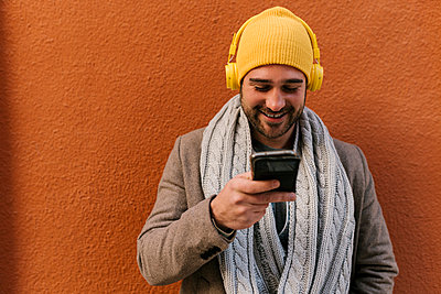 Mid adult man wearing knit hat using mobile phone while standing against wall - p300m2251662 by Ezequiel Giménez