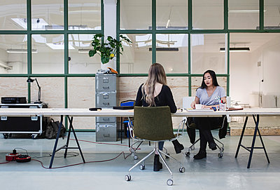 Two women working at desk in creative office - p426m1407180 by Maskot
