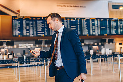 Mature businessman using mobile phone while walking in airport terminal - p426m1580060 by Maskot