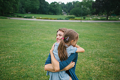 Mother and daughter embracing in the park - p586m1083450 by Kniel Synnatzschke