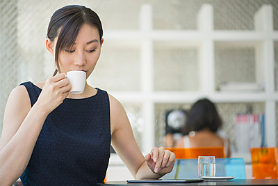 Woman drinking coffee in cafe, looking at digital tablet - p623m1086531f by Frederic Cirou