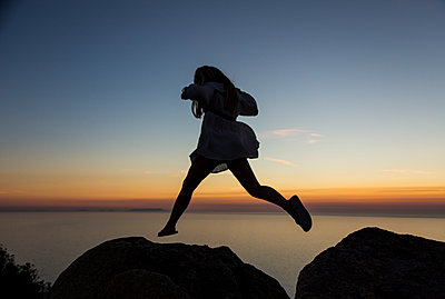 Girl jumps over rocks at sunset - p628m1476228 by Franco Cozzo